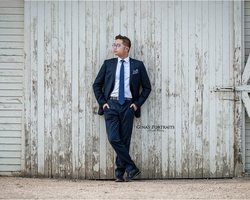 Male high school senior portrait leaning on barn wall
