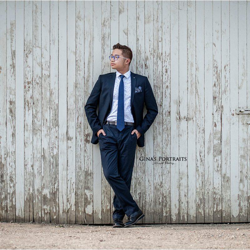 Male high school senior portrait leaning on barn wall