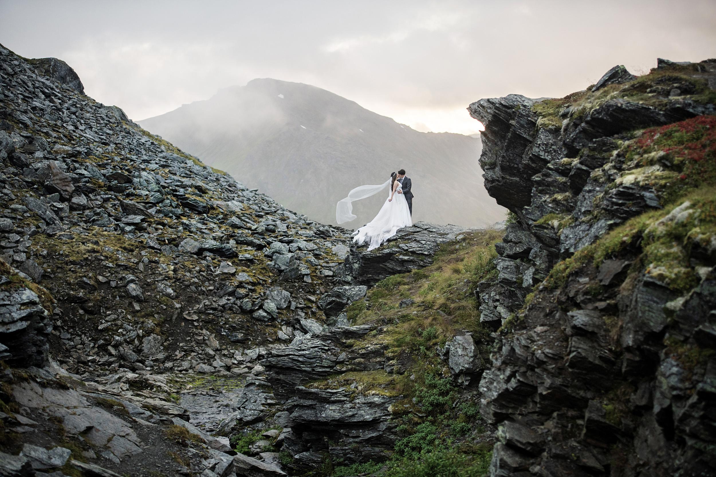 wedding couple standing on mountain top