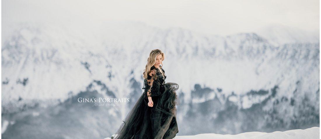 Model in winter backdrop wearing black gown