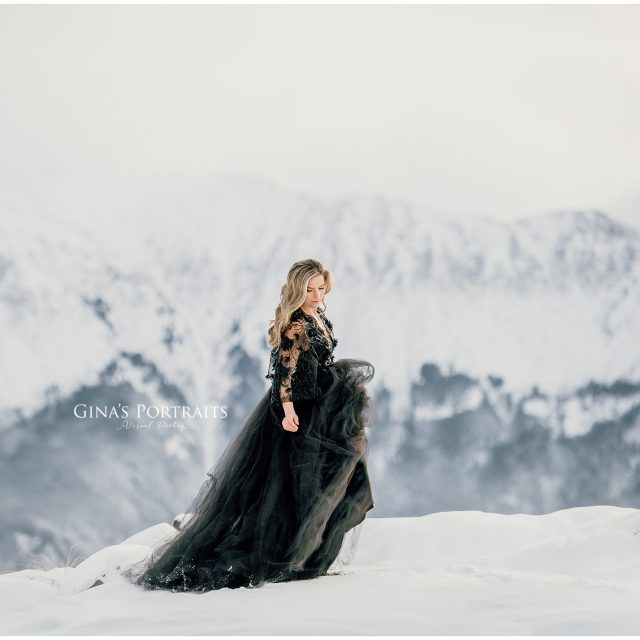 Model in winter backdrop wearing black gown