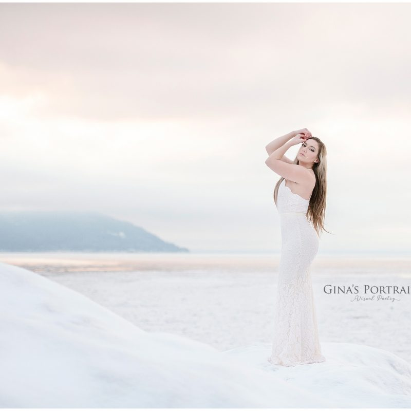 Model standing on cliff over looking ocean winter wearing white lace dress