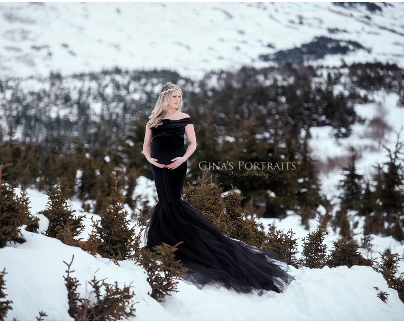 Pregnant lady in black dress in the winter mountain scene